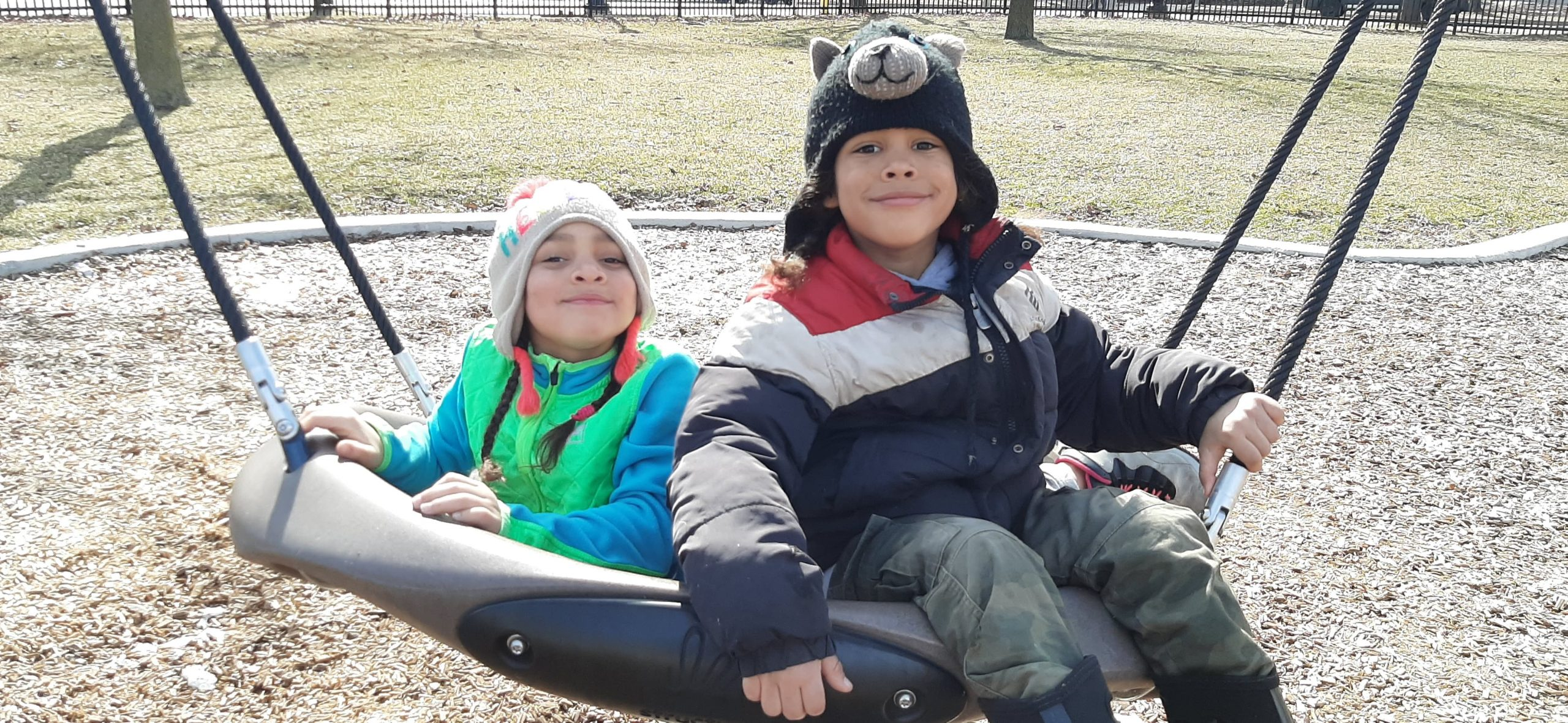 Twins, Alexandria and Sebastian are on a playground sitting side-by-side on a large swing and smiling.